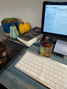 Desk with paperback, pumpkins,  keyboard and tablet on it